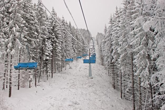 Seggiovia nella foresta di conifere di inverno nevoso