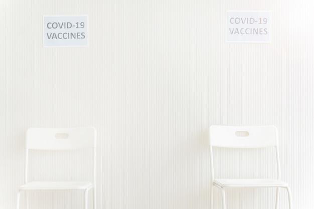 Sedie posizionate nella stazione di attesa per ottenere il vaccino contro il covid in clinica o in ospedale con muro bianco