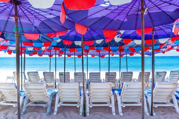Sedie sulla spiaggia sabbiosa con cielo blu e mare