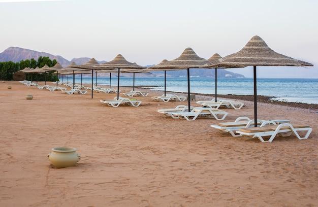 Sedie a sdraio, cestini di argilla e ombrelloni di paglia nella silenziosa spiaggia di taba