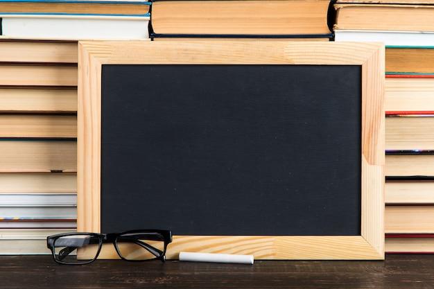 Lavagna nera, vetri e gesso, contro libri, copia spazio.