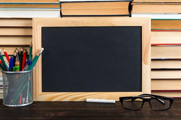Lavagna nera, occhiali, supporto con penne, matite e gesso, contro libri, copia spazio.