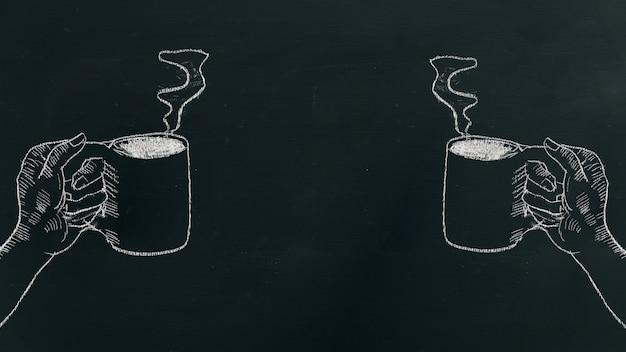 Segni la mano del gesso che disegna una tazza di caffè della tenuta della mano con vapore sul bordo nero