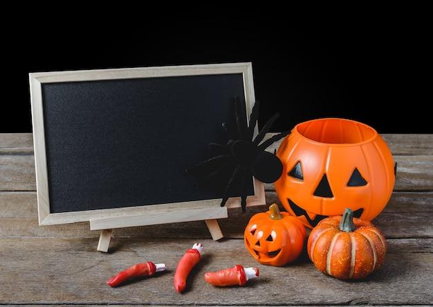 La lavagna sul basamento con halloween pumpkins, ragno nero sul pavimento di legno
