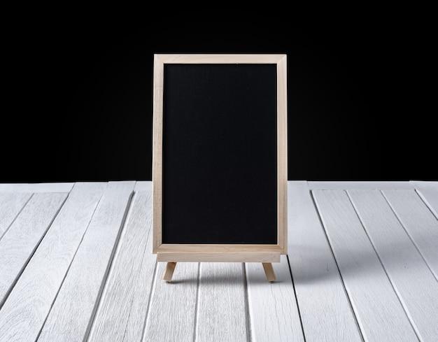 La lavagna sul basamento sul pavimento di legno e sullo sfondo nero