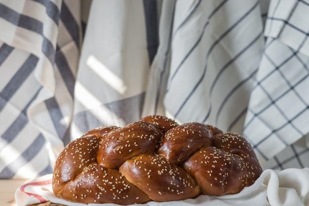 Pane di challah o pane ebreo tradizionale su un piatto di legno sulla tavola di legno