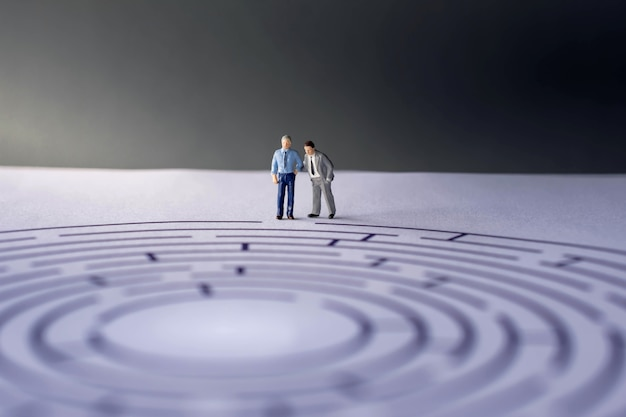 Sfida e concetto di successo. figura in miniatura di uomo d'affari sul labirinto