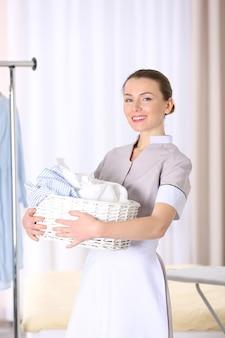 Cameriera che tiene cesto con biancheria in camera d'albergo
