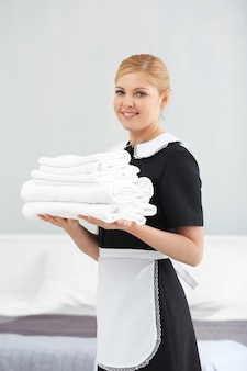 Cameriera che tiene un mucchio di asciugamani puliti in camera