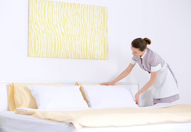 Cameriera che fa il letto in una stanza d'albergo