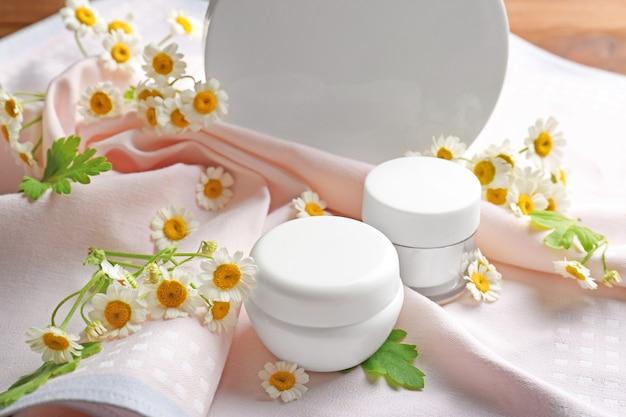 Prodotti cosmetici alla camomilla con fiori freschi e tessuto sul tavolo