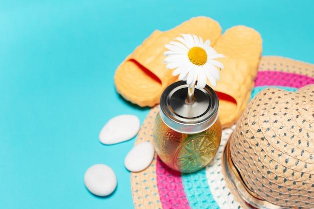 Fiore di camomilla in paglia di succo tazza di vetro, cappello estivo donna, pantofole gialle ciottoli lisci bianchi