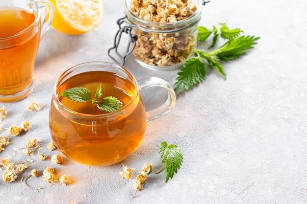 Camomilla e tisana con ortica sul tavolo, copia spazio, bevande alle erbe salutari e concetto di guaritore naturale