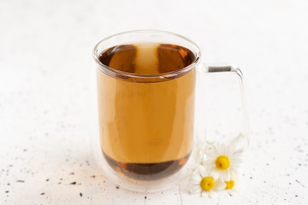 Camomilla e camomilla in tazza di vetro sul tavolo di cemento bianco. tè alle erbe. vista dall'alto. disposizione piatta.