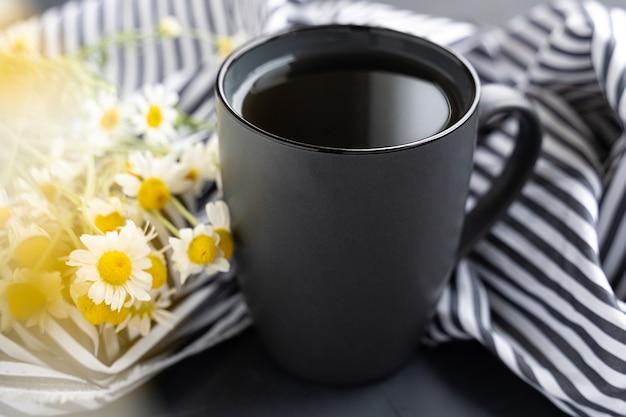 Camomilla e camomille in tazza di ceramica grigia sul tavolo di cemento nero. tè alle erbe. vista dall'alto. lay piatto Foto Premium