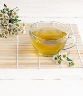 Tè alla camomilla in una tazza di vetro su un tavolo in legno bianco e fiori freschi di camomilla