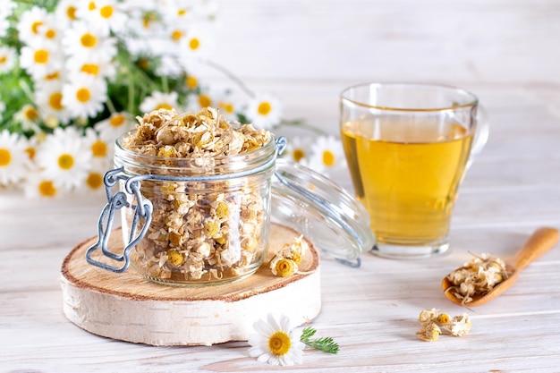 Tè di camomilla nel barattolo sul tavolo di legno bianco. fiori secchi e freschi