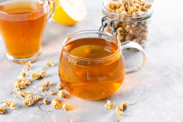 Tè alla camomilla sul tavolo, tazza trasparente con bevanda aromatica calda, relax e disintossicazione