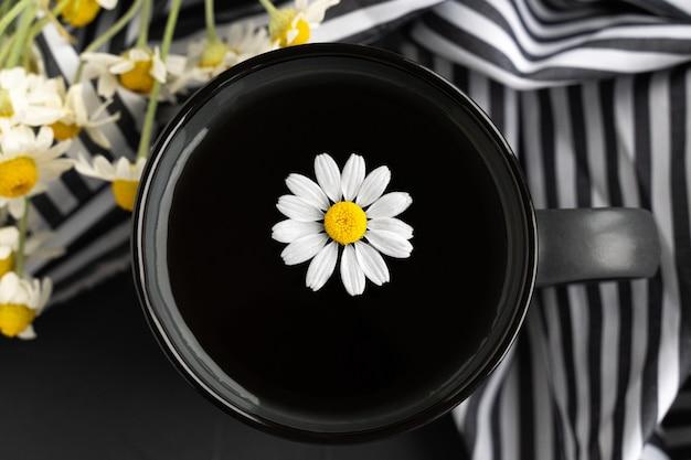 Tè alla camomilla con asciugamano da cucina e camomilla in tazza di ceramica grigia sul tavolo di cemento nero. tè alle erbe. vista dall'alto. disposizione piatta.