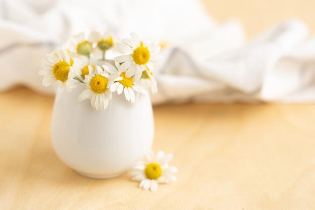 Camomille in tazza bianca sulla tavola di legno. tè alle erbe. vista laterale.foto orizzontale