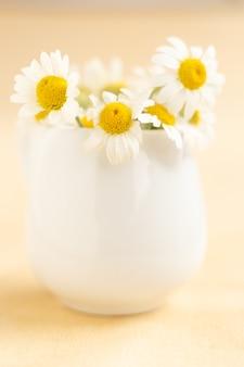 Camomille in tazza bianca sulla tavola di legno. tè alle erbe. vista laterale. foto verticale
