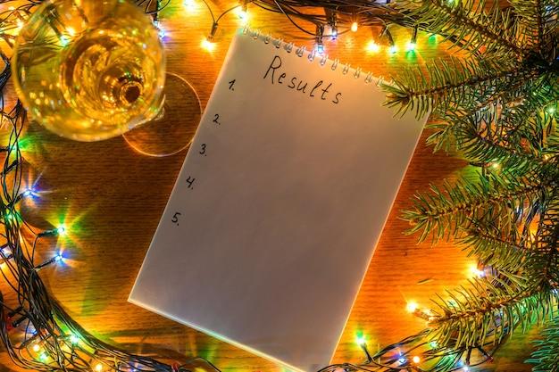 Sformato di champagne e un taccuino con i risultati dell'iscrizione sullo sfondo del nuovo anno.