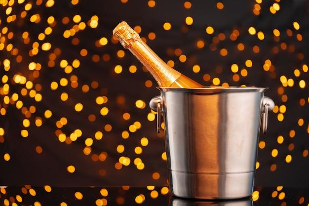 Bottiglia di champagne nel secchio contro vista frontale sfondo sfocato ghirlanda