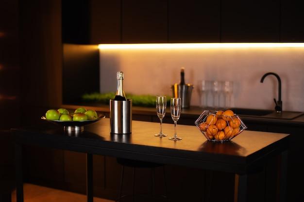 Bottiglia di champagne nel secchio con ghiaccio e bicchieri di champagne. interno soppalco cucina con zona cucina con isola.