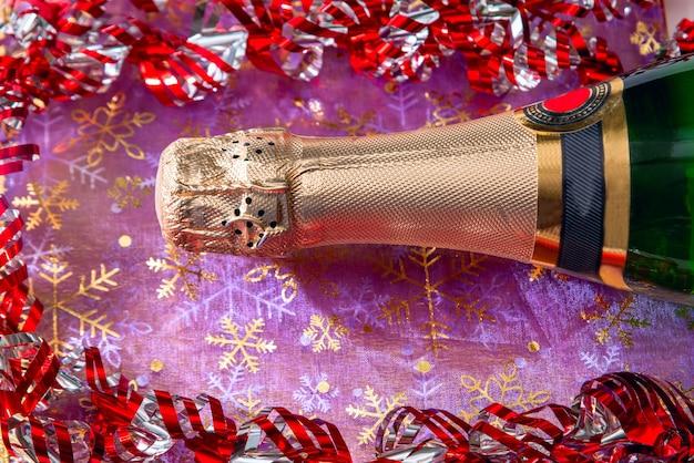 Bottiglia di champagne e orpelli festivi. anno nuovo e concetto di celebrazione