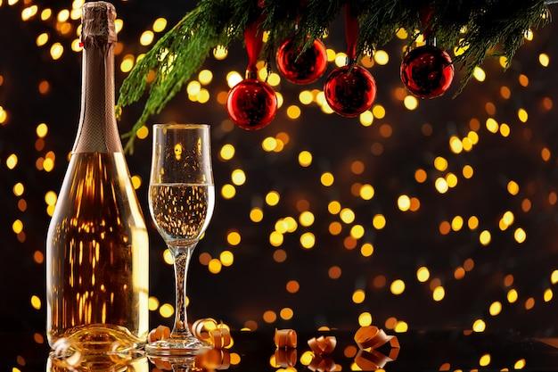 Bottiglia e vetro di champagne contro il fondo delle luci del bokeh