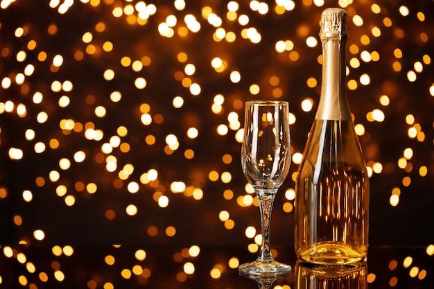 Bottiglia e vetro di champagne contro il fondo brillante delle luci del bokeh