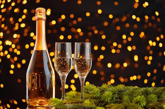Bottiglia di champagne e bicchieri su luci sfocate