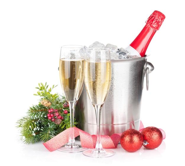 Bottiglia di champagne nel secchiello del ghiaccio, due bicchieri e decorazioni natalizie. isolato su sfondo bianco