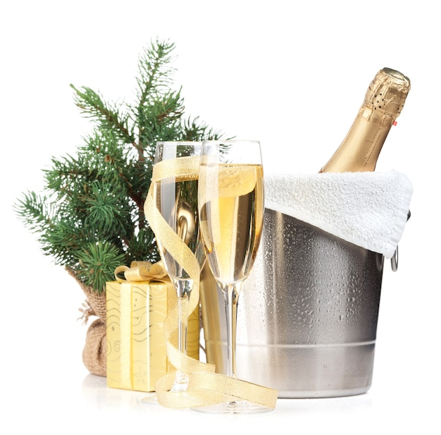 Bottiglia di champagne nel secchiello del ghiaccio, due bicchieri e regalo di natale. isolato su sfondo bianco