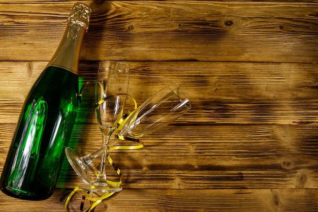 Bottiglia di champagne e due bicchieri di champagne vuoti su fondo di legno. vista dall'alto, copia spazio