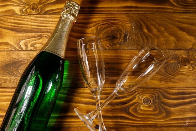 Bottiglia di champagne e due bicchieri di champagne vuoti su fondo di legno. vista dall'alto