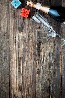 Bottiglia di champagne e due bicchieri vuoti su un legno