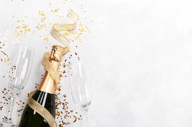 Bottiglia di champagne due bicchieri e coriandoli