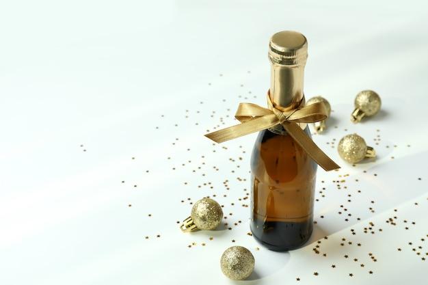 Bottiglia di champagne con fiocco, palline e glitter su sfondo bianco.
