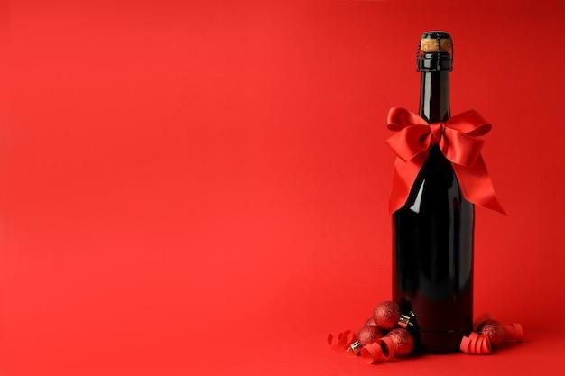 Bottiglia di champagne con fiocco e palline su sfondo rosso.
