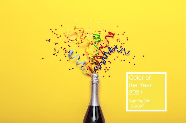 Bottiglia di champagne con stelle filanti colorate su giallo