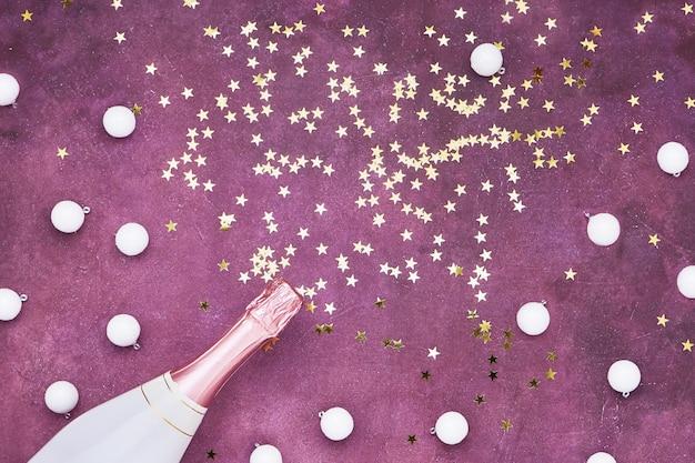 Bottiglia di champagne con coriandoli dorati sulla parete viola. lay piatto della celebrazione del natale