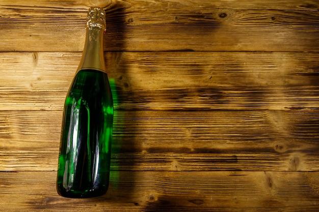 Bottiglia di champagne su fondo di legno. vista dall'alto, copia spazio