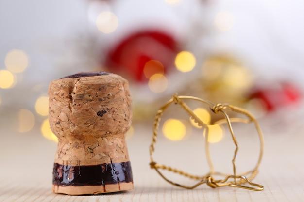 Tappo di champagne su sfondo di luci di natale