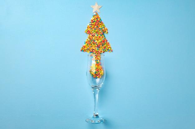 Bicchiere di champagne con coriandoli piatti laici sullo sfondo di natale