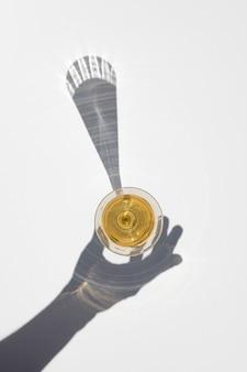 Bicchiere di champagne con ombra lunga e dura della mano