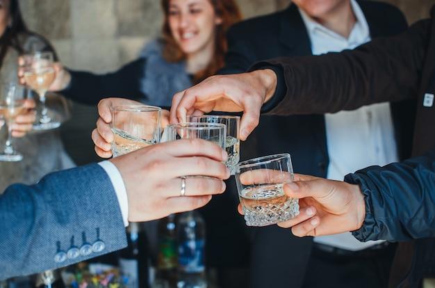 Bicchieri di champagne nelle mani di donne e uomini alla festa
