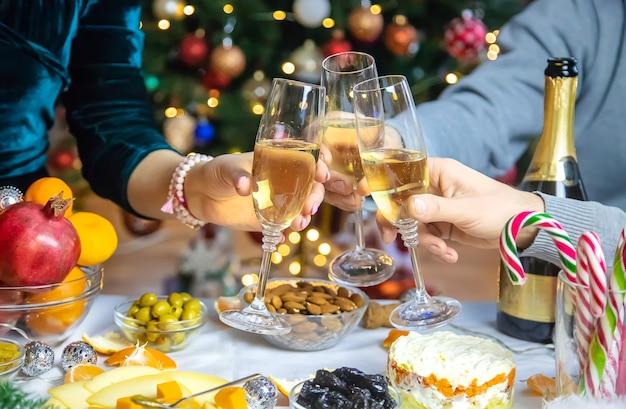 Champagne in mano sullo sfondo dell'albero di natale. persone.
