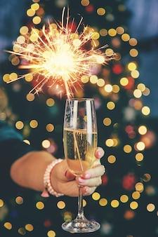 Champagne in mano sullo sfondo dell'albero di natale.