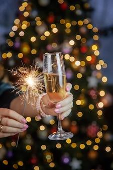 Champagne in mano contro l'albero di natale